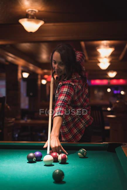 Donna che gioca a biliardo nel night club — Foto stock