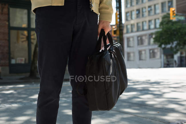 Mid section of man with a bag crossing the street — Stock Photo