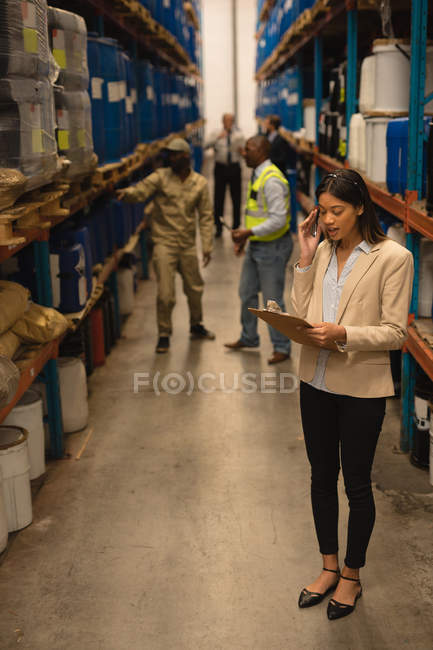 Supervisore donna che scrive su un blocco appunti in magazzino — Foto stock