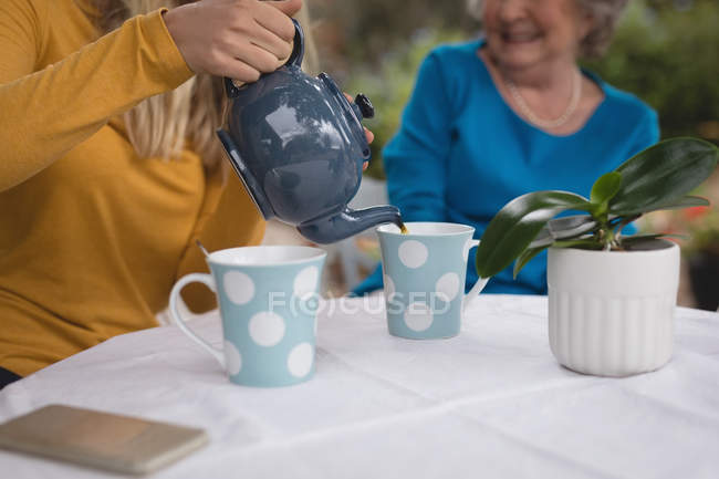 Granddaughter and grandmother having tea at backyard — Stock Photo