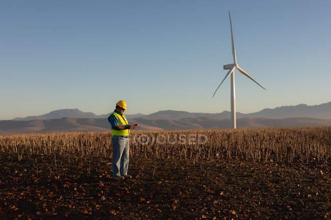Engenheiro usando telefone celular no parque eólico — Fotografia de Stock