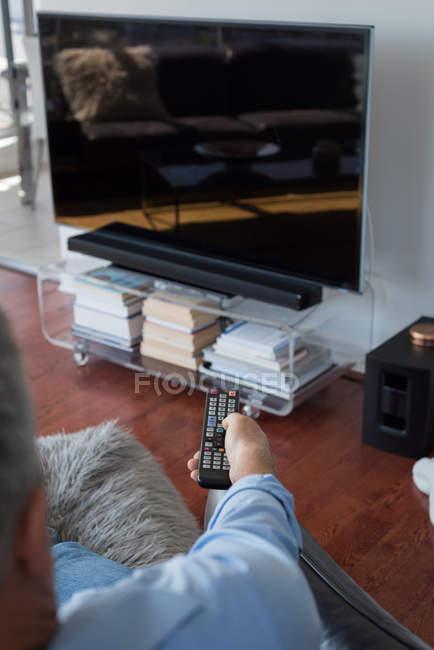Uomo che cambia canale mentre guarda la televisione in soggiorno a casa — Foto stock