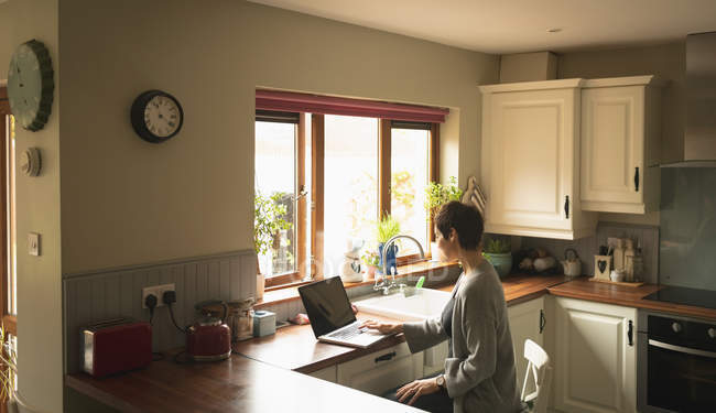 Woman using laptop in the kitchen at home — Stock Photo
