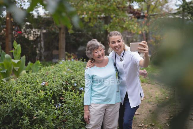Физиотерапевт и старшая женщина, принимая selfie в саду — стоковое фото