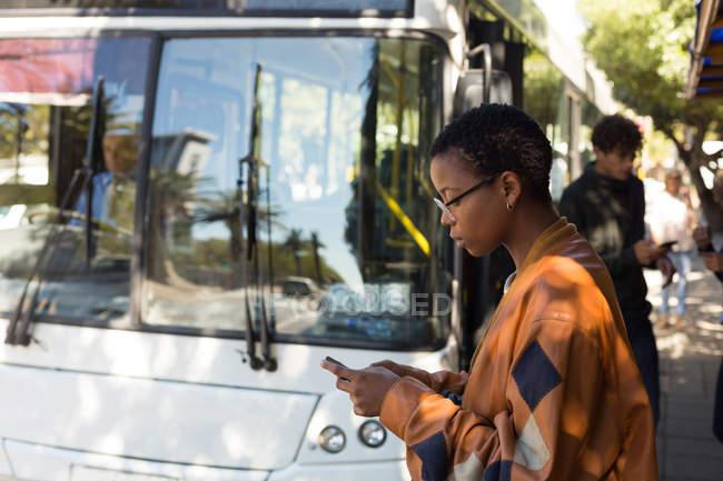Женщина разговаривает по мобильному телефону на автобусной остановке — стоковое фото