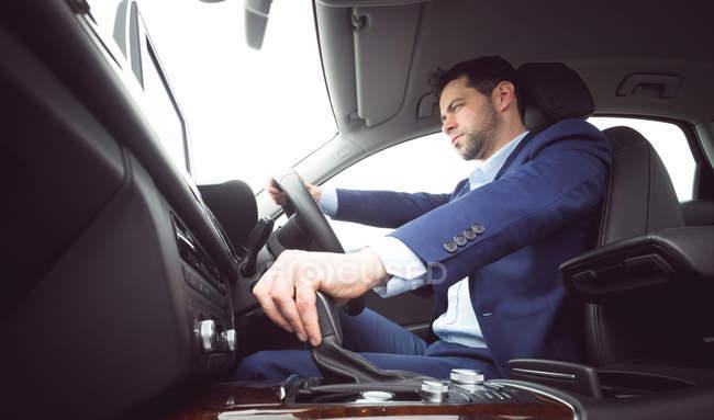 Умный бизнесмен за рулем автомобиля — стоковое фото