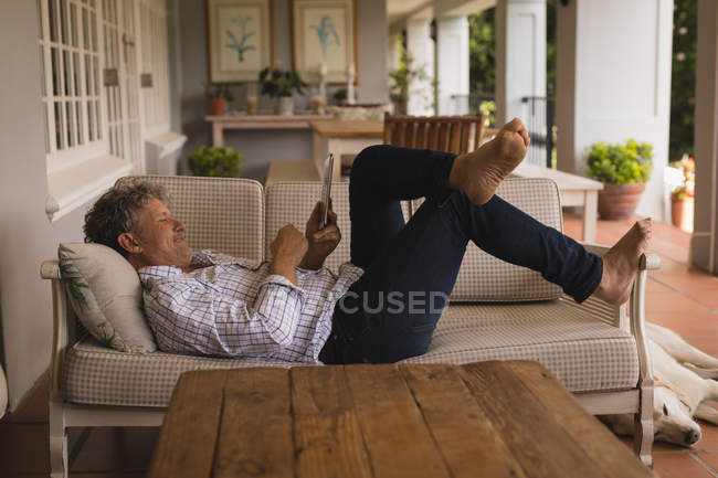 Senior man lying on the sofa and using digital tablet at home — Stock Photo