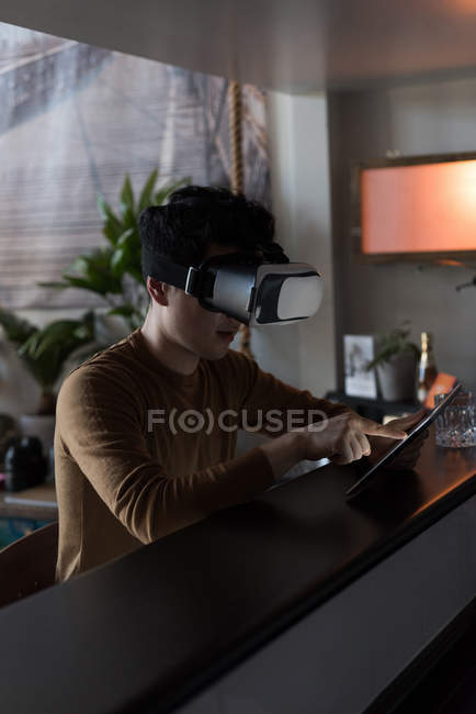 Чоловік у віртуальну реальність-гарнітура з застосуванням цифровий планшетний вдома — стокове фото