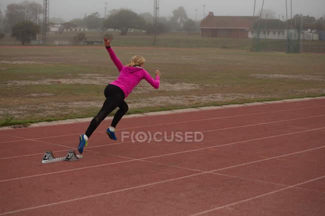 Female athlete running from starting block on the running track — Stock Photo