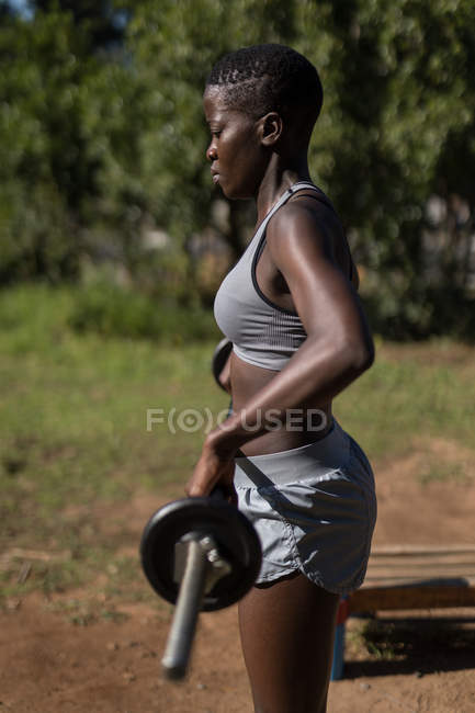 Решительная спортсменка, поднимающая штангу — стоковое фото