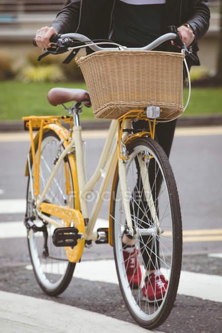 Sezione bassa della donna con la strada di attraversamento della bicicletta — Foto stock
