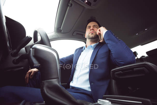 Businessman talking on mobile phone in a modern car — Stock Photo