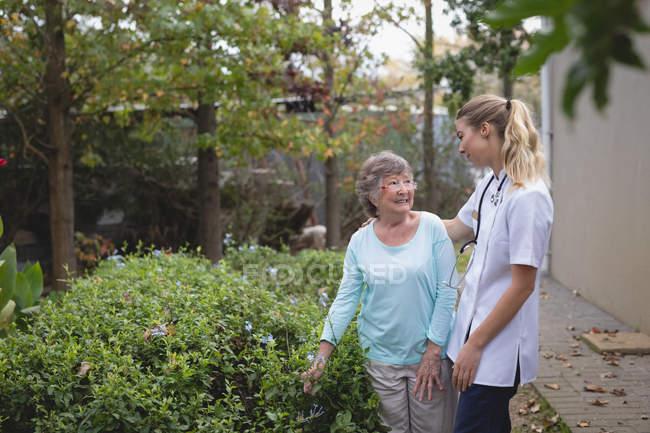 Физиотерапевт и старшая женщина, говорить на заднем дворе дома — стоковое фото