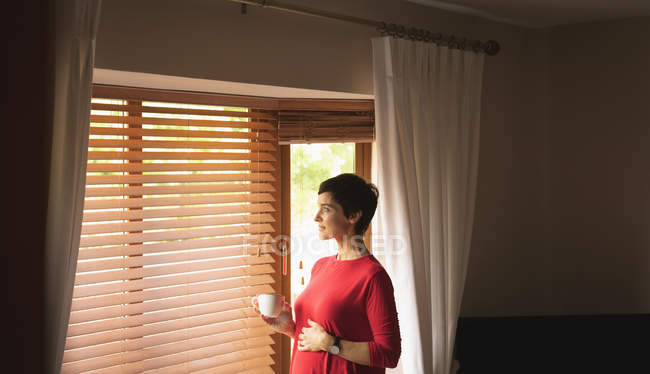 Donna che guarda attraverso la finestra mentre prende un caffè in soggiorno a casa — Foto stock