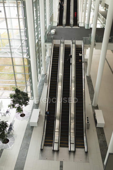 High angle view of businesspeople on the escalator in office — Stock Photo