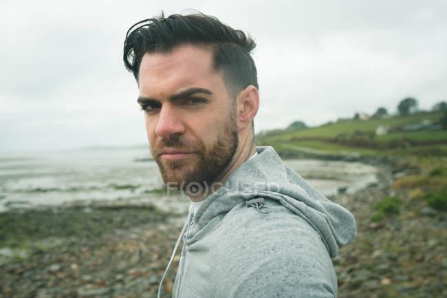 Retrato de confianza forma hombre de pie a orillas del mar - foto de stock