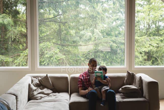Padre e figlio utilizzano tablet digitale in soggiorno a casa — Foto stock