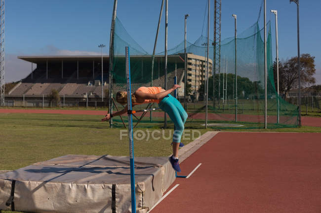 Female athlete practicing high jump at sports venue — Stock Photo
