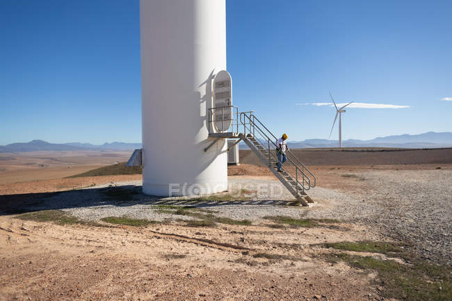 Engineer climbing down the stairs of a wind mill at a wind farm — Stock Photo