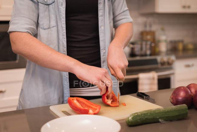 Femme coupant poivron dans la cuisine à la maison — Photo de stock
