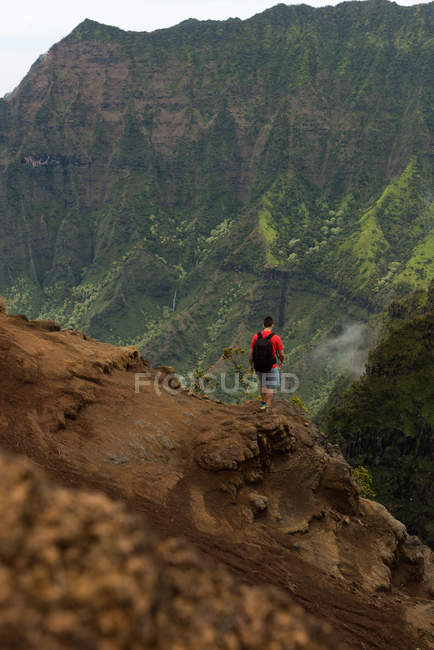 Hiker standing at the edge of mountain at Na Pali Coast State Park — Stock Photo