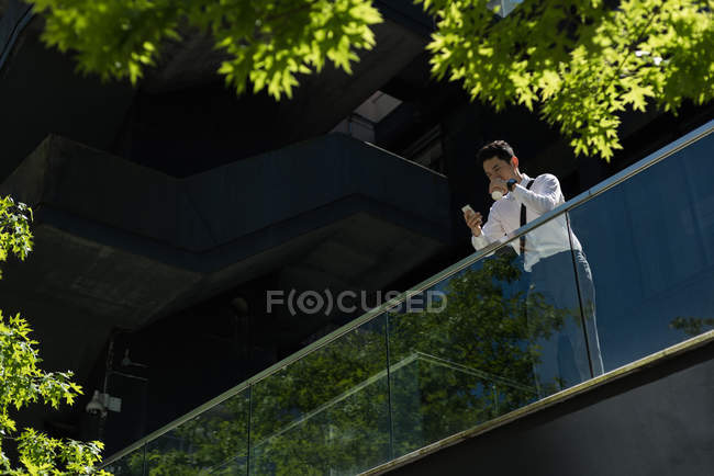 Man having using mobile phone and having coffee in office balcony on a sunny day — Stock Photo