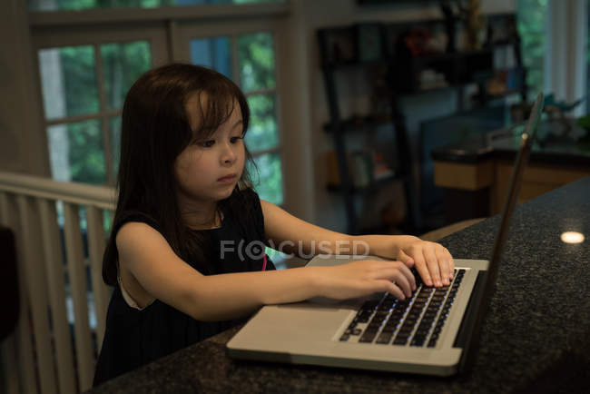 Adorable girl using laptop at home — Stock Photo