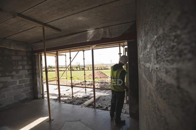 Вид сзади инженера с уровня датчика работы на строительной площадке — стоковое фото