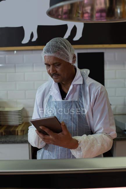 Attentive butcher using digital tablet in butcher shop — Stock Photo