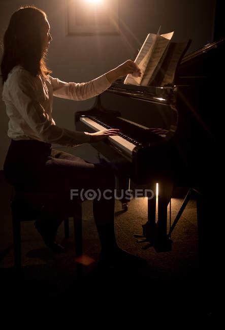 Seitenansicht einer Schülerin, die in der Musikschule Klavier spielt — Stockfoto