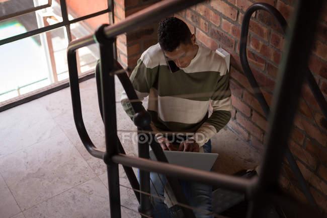 Человек разговаривает по мобильному телефону во время использования ноутбука дома — стоковое фото