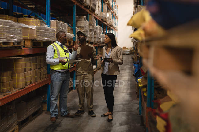 Staff discussing over clipboard in warehouse — Stock Photo