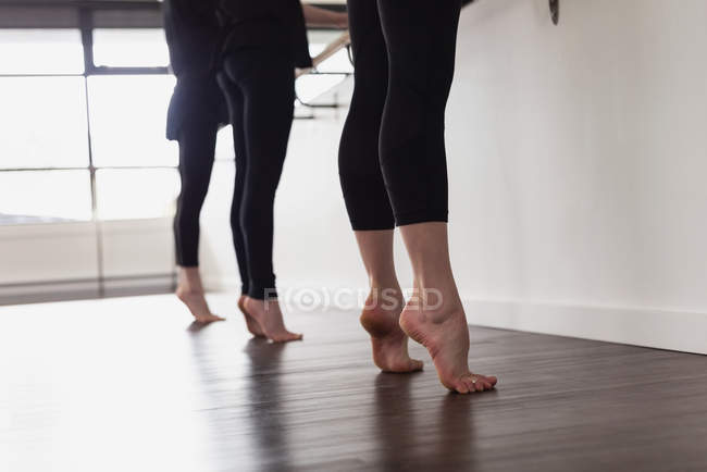 Low section of group of women standing on tip toe on wooden floor — Stock Photo