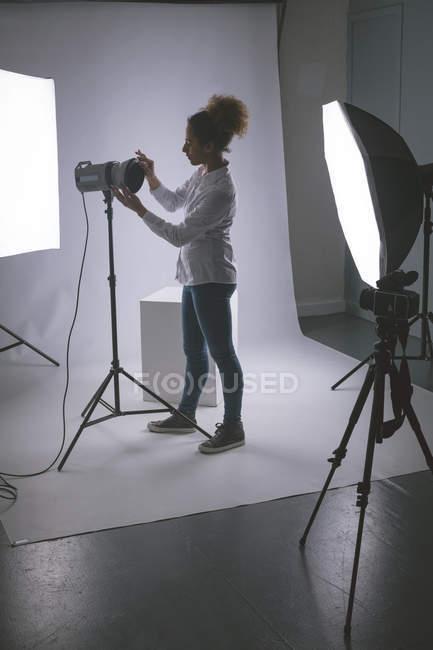 Female photographer adjusting strobe lights in photo studio — Stock Photo
