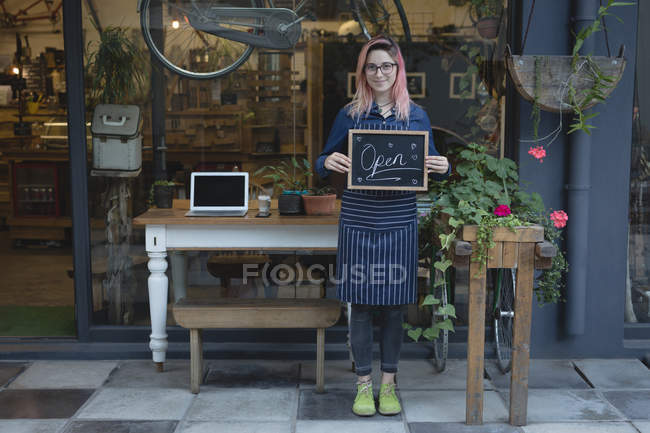 Баріста стоячи з відкритим Вивіска зовні кафе — стокове фото