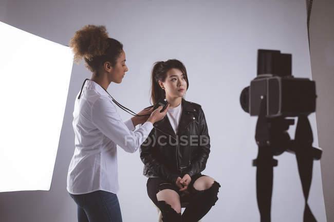 Feminino fotógrafo gravando uma entrevista usando o gravador de voz no estúdio de fotografia — Fotografia de Stock