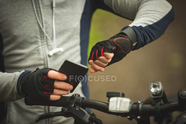 Mid section of cyclist checking time while using mobile phone in forest — Stock Photo