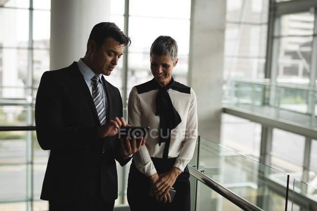Deux hommes d'affaires discutent sur la tablette au bureau — Photo de stock