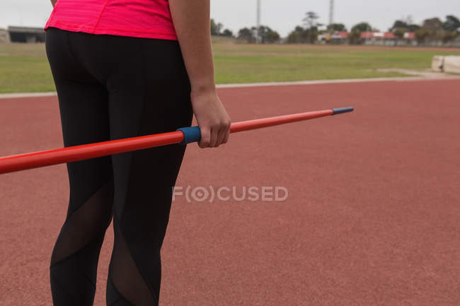 Mid section of female athlete practicing javelin throw — Stock Photo