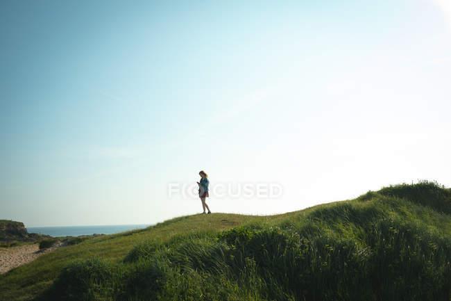 Donna che utilizza il telefono cellulare mentre in piedi sulla collina vicino alla costa del mare in una giornata di sole — Foto stock