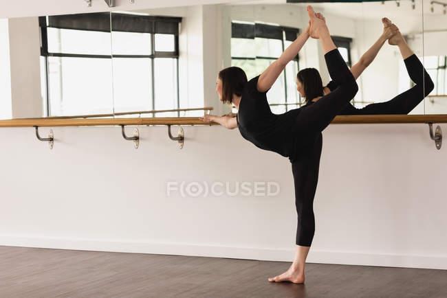 Jovem praticando perna esticando no ginásio — Fotografia de Stock