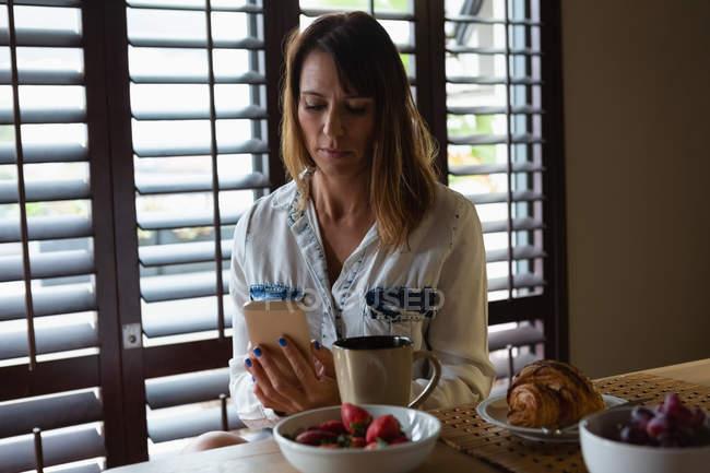 Donna che utilizza il telefono cellulare in cucina a casa — Foto stock