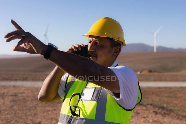 Engineer talking on mobile phone at wind farm — Stock Photo