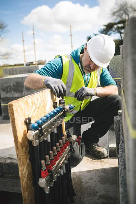 Travailleur de la construction examinant les tuyaux sur place — Photo de stock