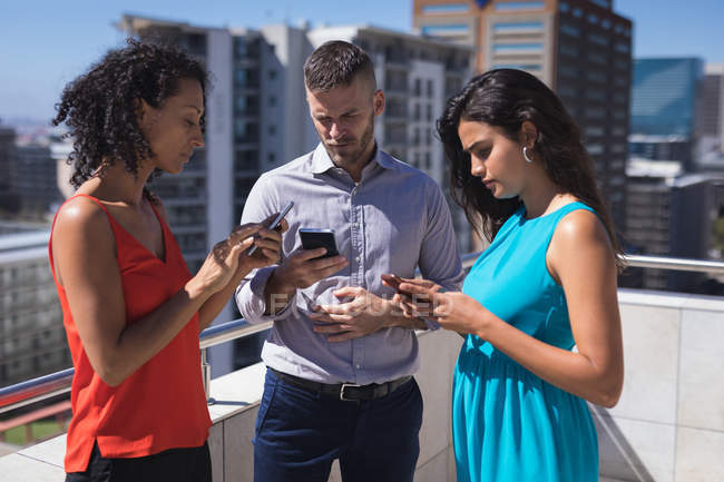 Führungskräfte nutzen Smartphone an einem sonnigen Tag auf der Büroterrasse — Stockfoto