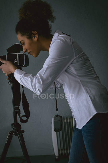 Female photographer clicking photos with digital camera in photo studio — Stock Photo