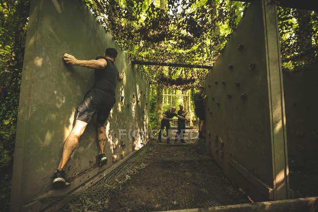 Ajustement des hommes sur des parcours d'obstacles au camp d'entraînement de formation — Photo de stock