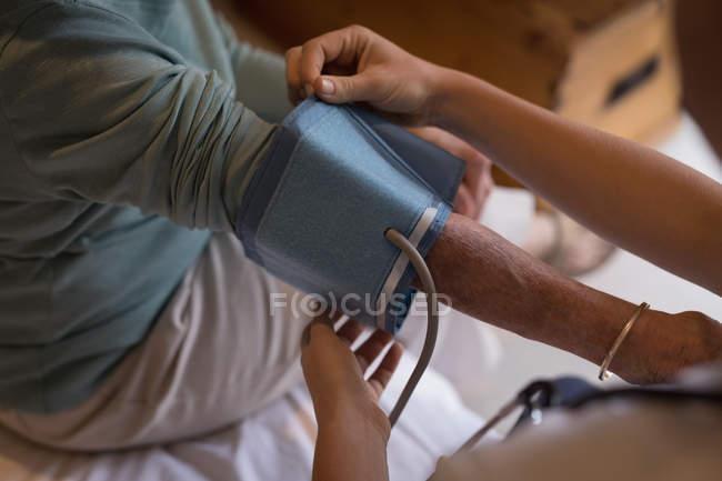 Nahaufnahme des Physiotherapeuten, der den Blutdruck der Seniorin überprüft — Stockfoto
