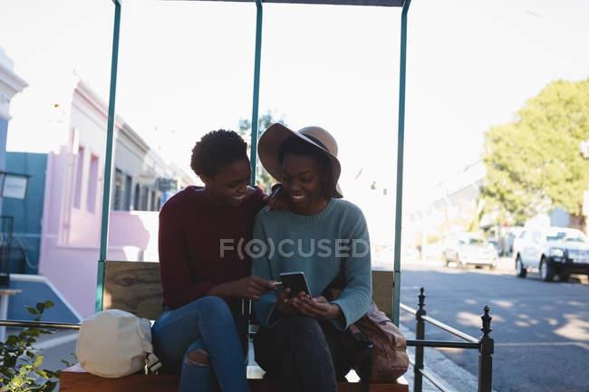 Heureux jumeaux frères et sœurs uisng téléphone mobile dans la rue de la ville — Photo de stock