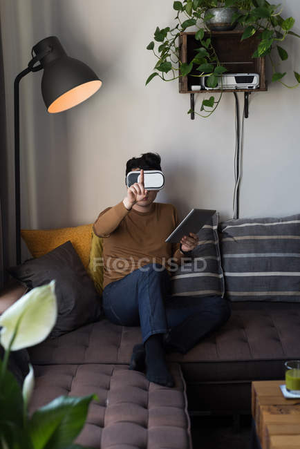 Чоловік у віртуальну реальність-гарнітура з застосуванням цифровий планшетний у вітальні на дому — стокове фото